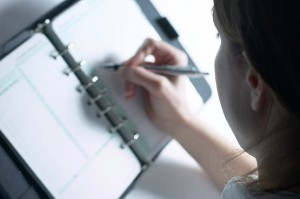 Caucasian businesswoman writing in day planner with pen 1