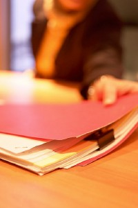 Person reaching for red file folder