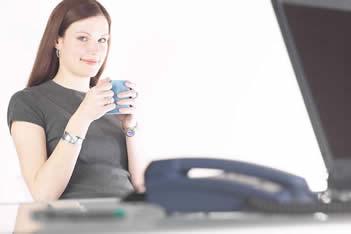 Smilingwomandrinkingcoffeeatherdesk