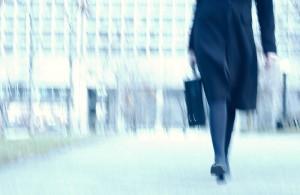 Blur of businesswoman walking along path in park